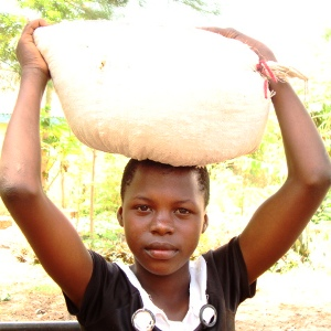 Young woman in Musoma orphans program with bag of maize on her head.
