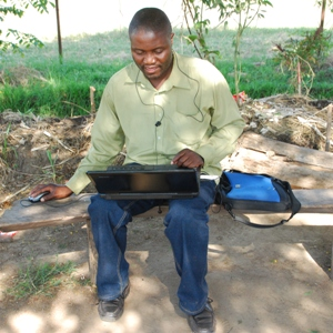Permaculture volunteer from Zimbabwe working on laptop at Kinesi plot.