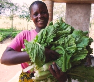 Woman smiling holding Chinese cabbage.