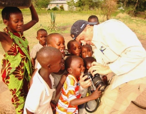 International volunteer showing a group of excited children a photo on his camera.