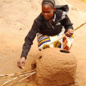 Woman working with alternative cooking technologies, rocket stove.