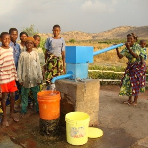 Woman pumping water with BluePump into bucket with children around well.